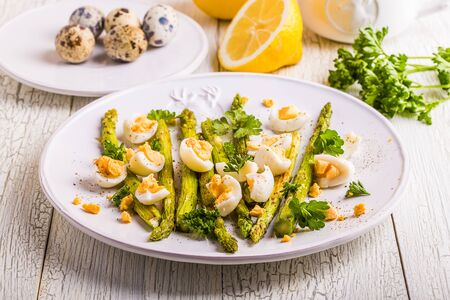 Grilled asparagus with quail eggs on a white wooden background Stock Photo