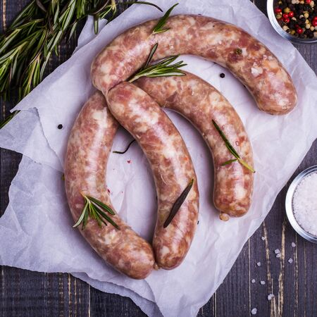 white meat: Raw sausage with spices on a dark wooden background