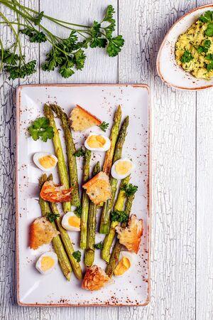huevos de codorniz: Espárragos a la plancha con huevos de codorniz sobre un fondo de madera blanca