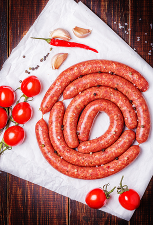 Raw lamb sausage with ingredients for salsa on a dark background 스톡 콘텐츠