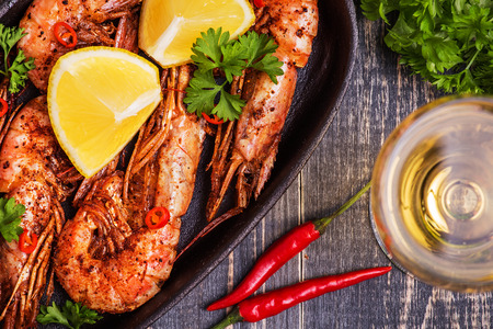 prepared shellfish: Fried shrimp with lemon and white wine on a dark wooden background