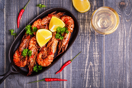 Fried shrimp with lemon and white wine on a dark wooden background