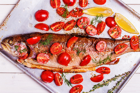 Baked trout with marinated tomatoes on a metal baking sheet