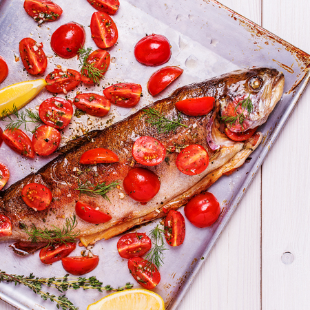 metal sheet: Baked trout with marinated tomatoes on a metal baking sheet