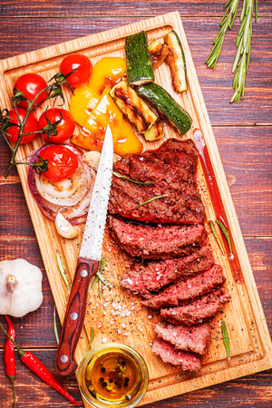 red chili pepper: BBQ steak with grilled vegetables on cutting board on dark wooden background.