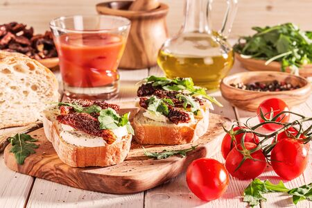 sundried: Sandwich with mozzarella, sun-dried tomatoes and arugula on a white background. Stock Photo