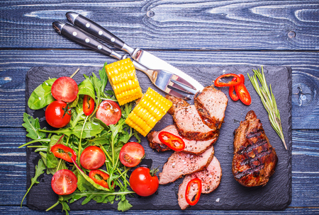 the lamb: BBQ lamb steak with vegetable salad and corn on stone board on dark wooden background.
