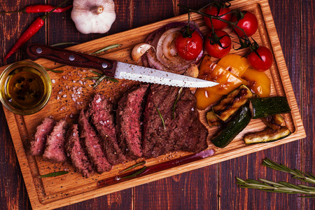 BBQ steak with grilled vegetables on cutting board on dark wooden background.