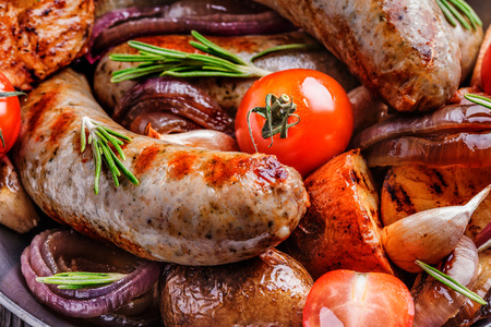Grilled sausages and vegetables  in  rustic style. Selective focus. Imagens