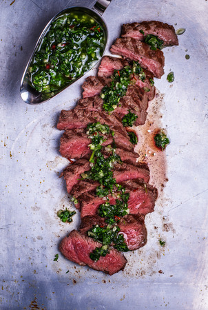 Sliced beef barbecue steak with chimichurri sauce, top view, rustic metal background Imagens