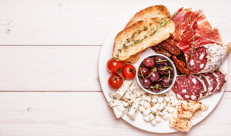 Snack set. Variety of cheese and meat, olives, tomatoes on white background, top view, copy space.