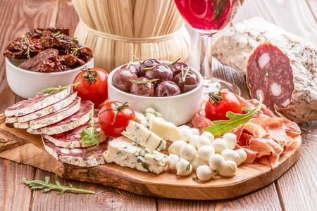 jamones: establece aperitivo vino. Variedad de queso y carne en el fondo oscuro. enfoque selectivo.