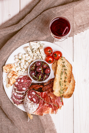 white cheese: Wine snack set. Variety of cheese and meat, olives, tomatoes on white background, top view.