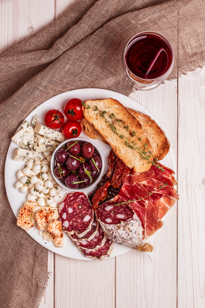 olive: Wine snack set. Variety of cheese and meat, olives, tomatoes on white background, top view.