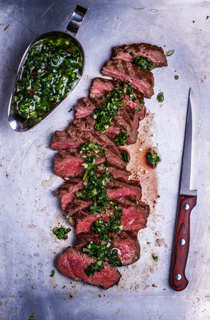 Sliced beef barbecue steak with chimichurri sauce, top view, rustic metal background Stockfoto