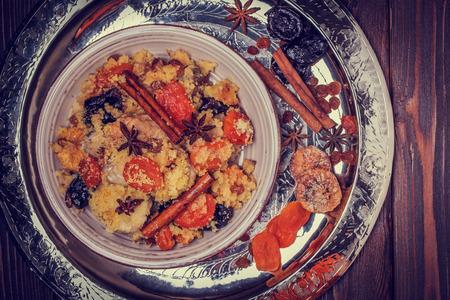 comida arabe: Pollo marroquí tradicional con frutas secas y especias, foco selectivo.