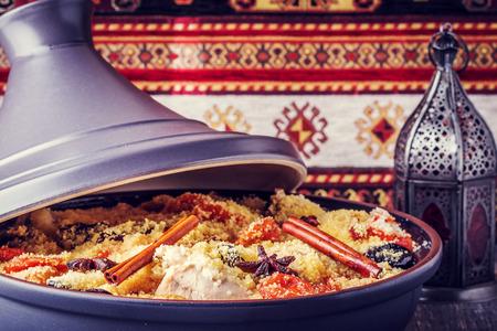 Traditionele Marokkaanse tajine van kip met gedroogde vruchten en kruiden, selectieve aandacht. Stockfoto