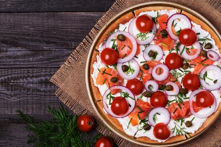 comida gourmet: Pizza de salm�n escandinavo con queso crema, alcaparras, tomate y cebolla. Vista superior.