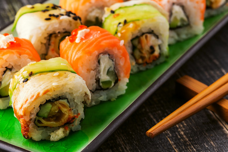 sushi chopsticks: Sushi set: sushi roll with salmon and sushi roll with smoked eel, selective focus.