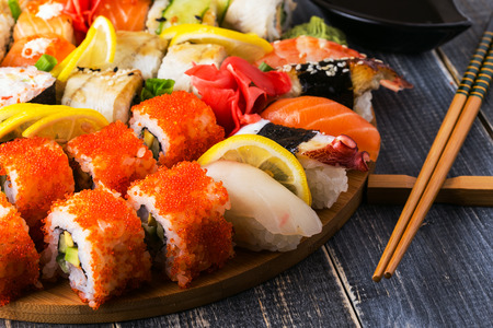 Sushi Set: sushi and sushi rolls on wooden plate, selective focus. Stockfoto