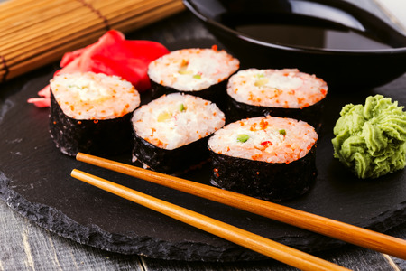 comida japonesa: Sushi roll with crab, spicy sauce, cucumber and tobiko caviar, selective focus.