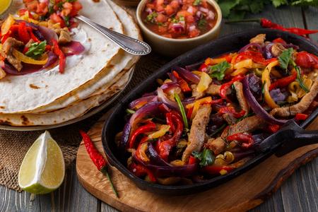 bailar salsa: fajitas de carne de cerdo con cebolla y el pimiento de color, que se sirve con tortillas, salsa y crema agria, el enfoque selectivo. Foto de archivo