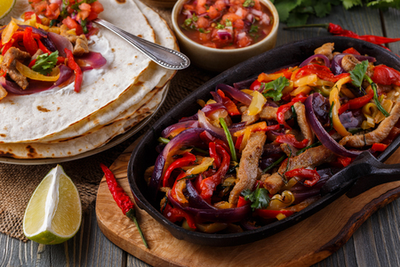 salsa: Pork fajitas with onions and colored pepper, served with tortillas, salsa and sour cream, selective focus.