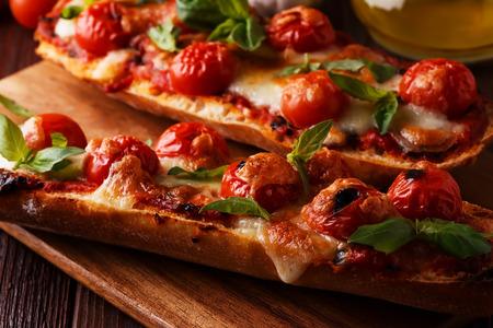 comida italiana: Pizza margarita with mozzarella and cherry tomatoes, basil on a baguette, selective focus. Foto de archivo