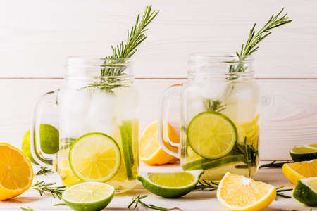 limonada: Limonada casera con lima, limón, romero en tarro de albañil en el fondo blanco de madera.