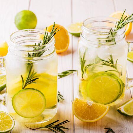 jag: Homemade lemonade with lime, lemon, rosemary in  mason jar on  wooden white background.
