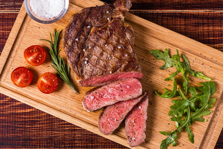 Ribeye steak with arugula and tomatoes on dark wooden background. 스톡 콘텐츠