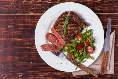 meat food: Ribeye steak with arugula and tomatoes on  dark wooden background. Stock Photo