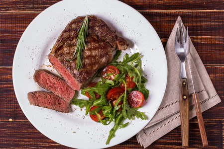 Ribeye steak with arugula and tomatoes on  dark wooden background. Stockfoto