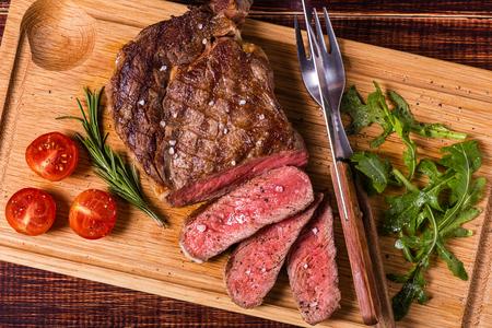 Ribeye steak with arugula and tomatoes on dark wooden background. Foto de archivo