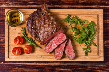 Ribeye steak with arugula and tomatoes on dark wooden background. Banque d'images