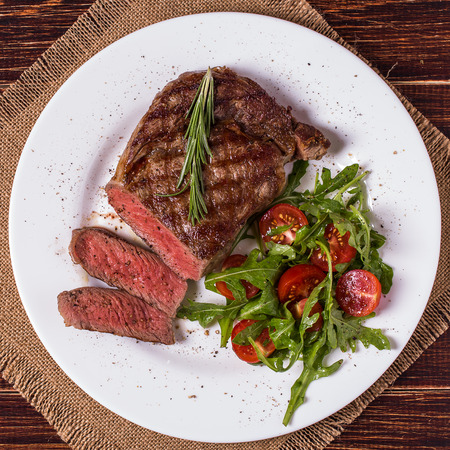 Ribeye steak with arugula and tomatoes on  dark wooden background. Zdjęcie Seryjne