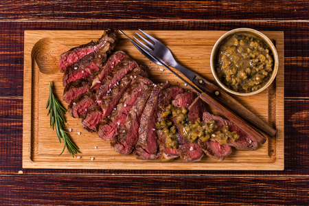 Ribeye steak and mustard sauce with pickles on dark wooden background. Imagens