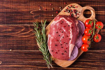 Raw fresh meat Ribeye Steak, seasoning  on dark background.