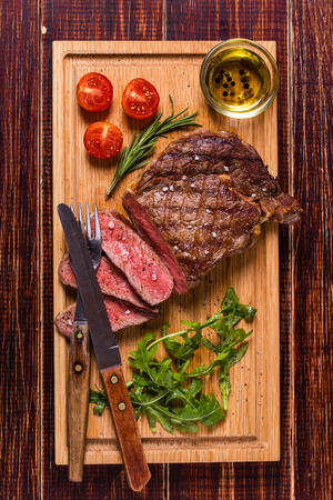Ribeye steak with arugula and tomatoes on dark wooden background. Imagens