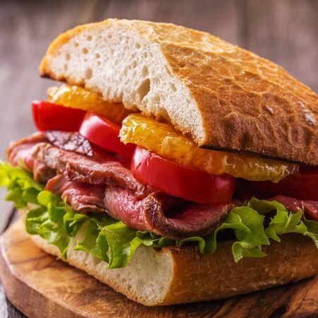 steak sandwich: Juicy steak sandwich with vegetables and slices of orange, selective focus.