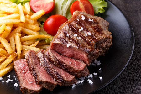 New York steak with french fries and salad. Imagens