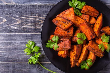 fries: Homemade Cooked Sweet Potato with spices and herbs on dark background. Stock Photo