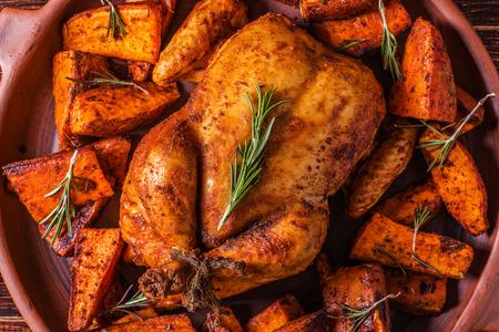 Zelfgemaakte Paprika en Herb Hele kip met kruiden zoete aardappel op een donkere achtergrond. Stockfoto