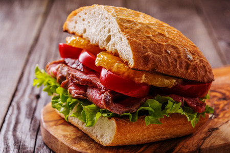 Sappige steak sandwich met groenten en plakken van sinaasappel, selectieve aandacht. Stockfoto