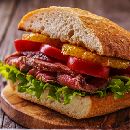 Juicy steak sandwich with vegetables and slices of orange, selective focus.