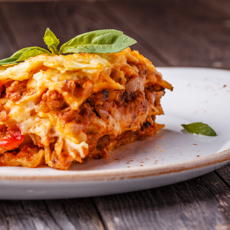 browned: Traditional lasagna made with minced beef bolognese sauce and bechamel sauce  topped with basil leaves. Stock Photo