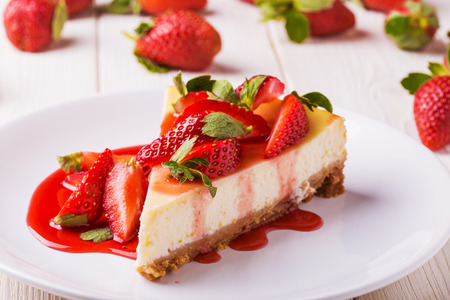 Delicious homemade cheesecake with strawberries  on  white wooden table.