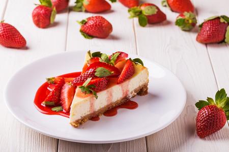 fresa: pastel de queso hecho en casa delicioso con las fresas en la mesa de madera blanca. Foto de archivo
