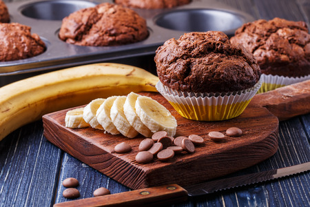eating banana: Chocolate muffins with banana on dark background, selective focus.