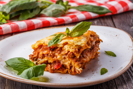 Traditional lasagna made with minced beef bolognese sauce and bechamel sauce  topped with basil leafs.